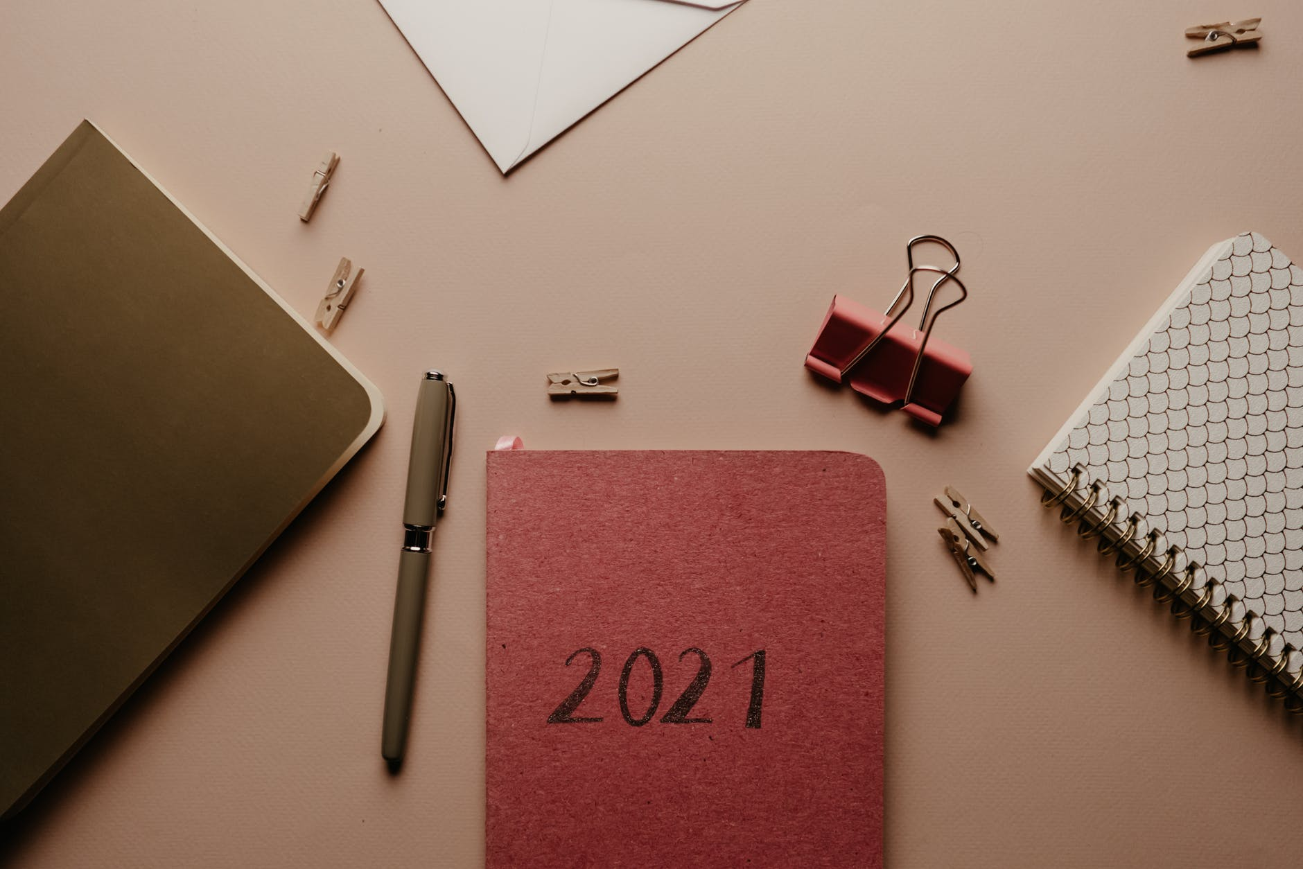 "A planner with ""2021"" sits on a desk, including a few pieces of stationery."