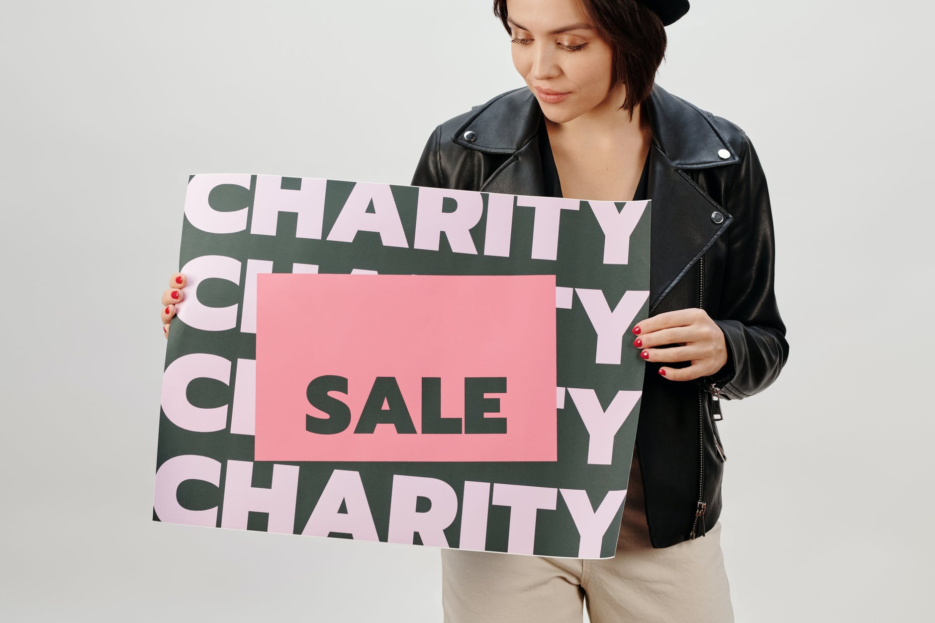 "Woman holds a sign that says ""Charity Sale""."