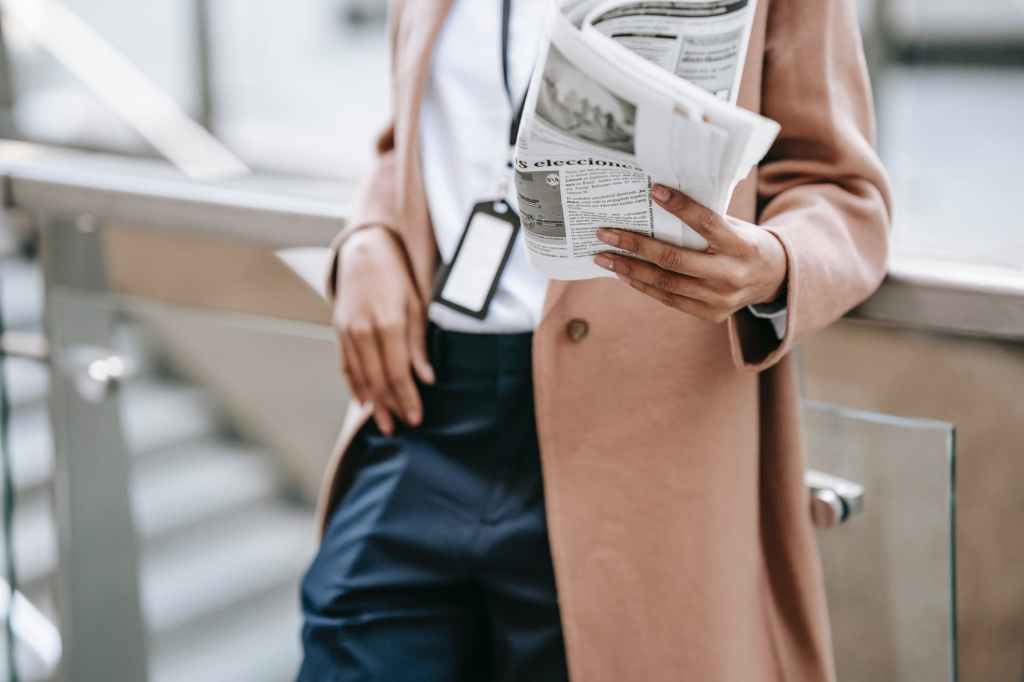 Woman reading newspaper in a long pink coat.