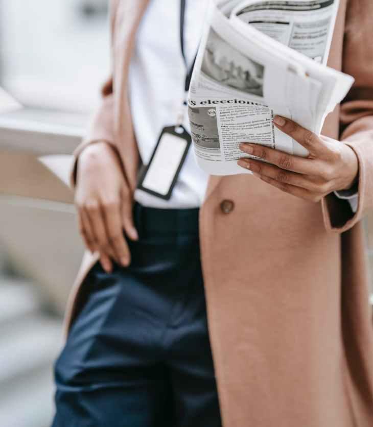 businesswoman reading newspaper near fence