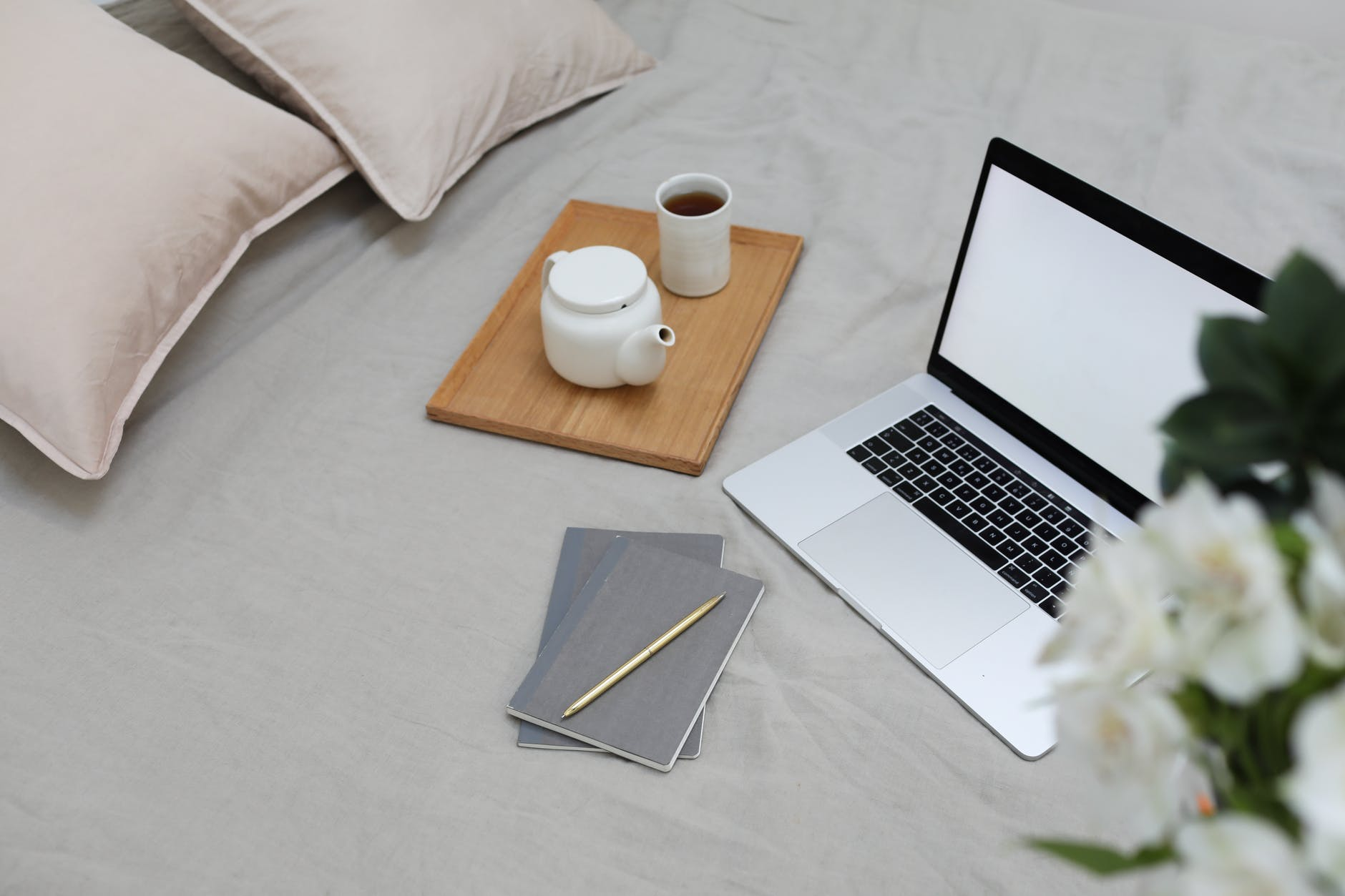 Open laptop and cup on tea on a bedspread, along with some cushions and notebooks.
