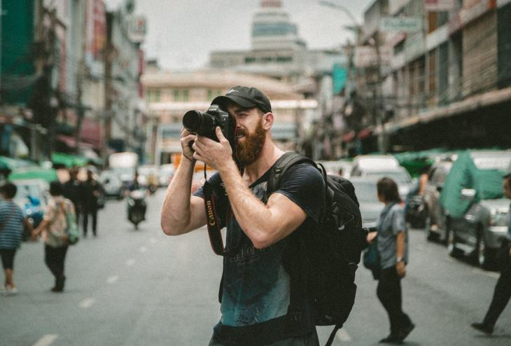 A man points a camera in the middle of a street