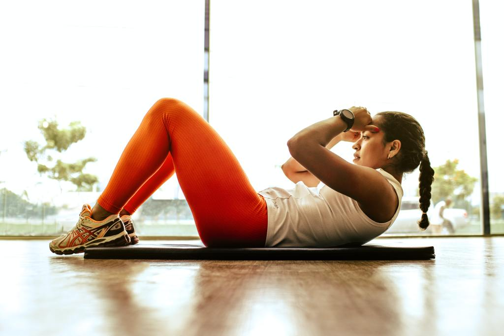 Woman does sit-ups on a mat.