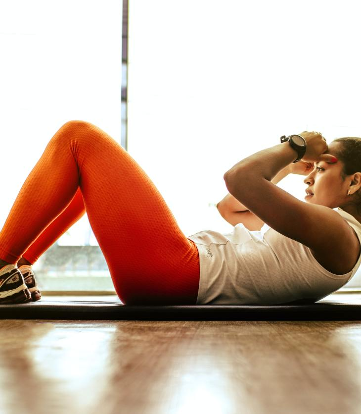 Woman does a crunch on an exercise mat