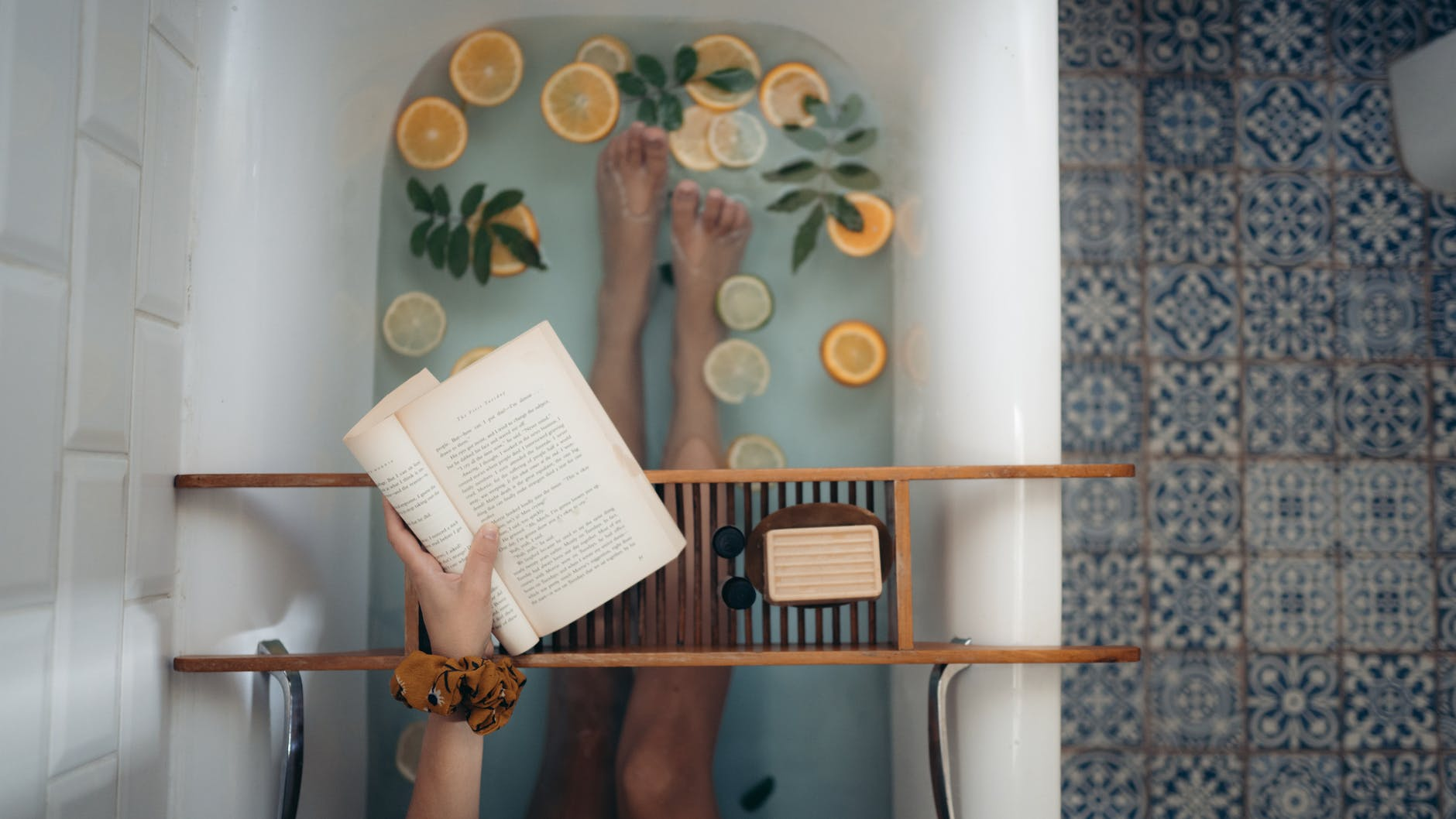 A woman lays in a luxurious bath, reading a book and surrounded by fresh fruit.