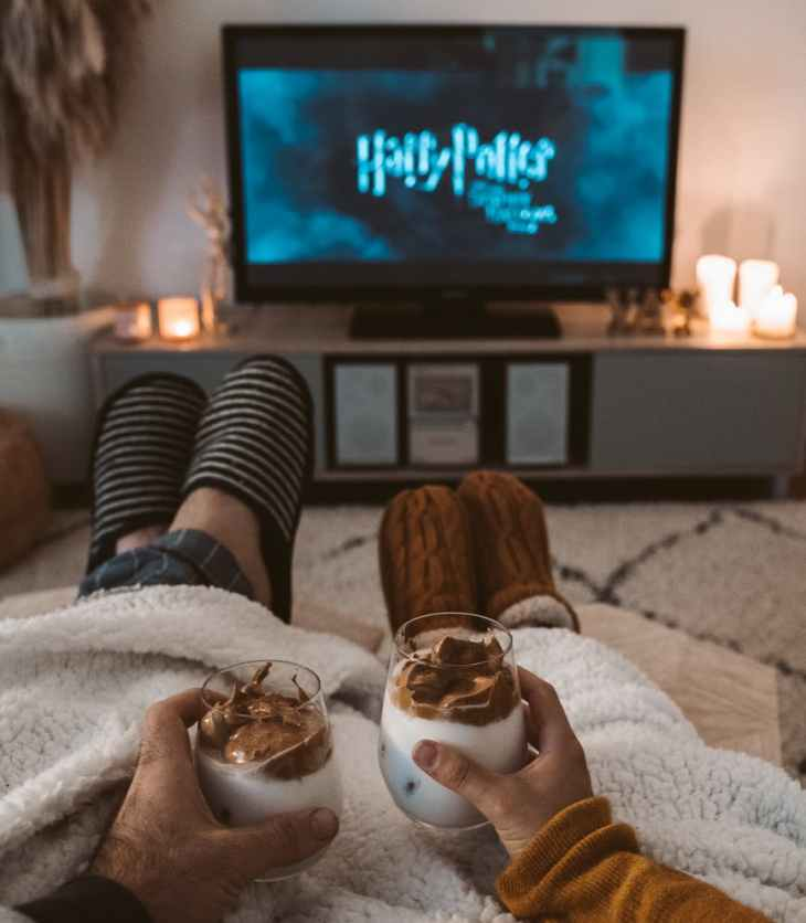 Two people watch Harry Potter under a blanket with drinks