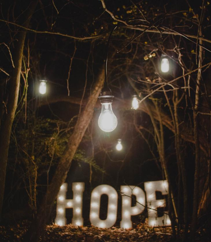 """Word """"Hope"""" lit up in the middle of the trees"""