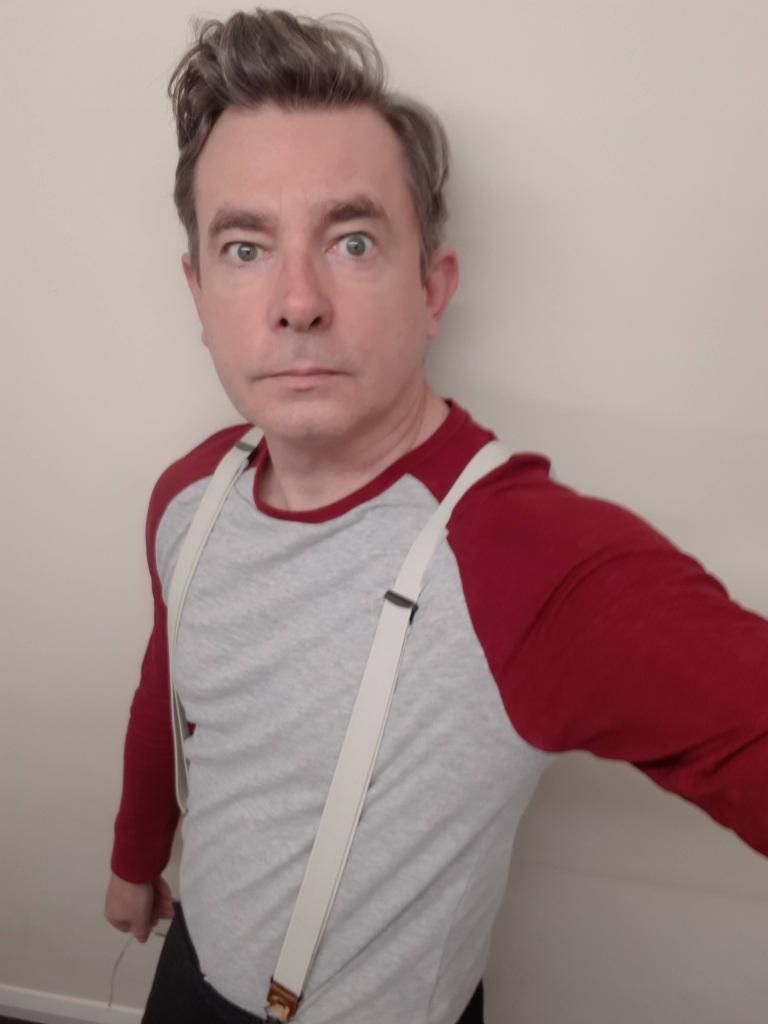 A man takes a selfie, he has wide eyes and is wearing suspenders.
