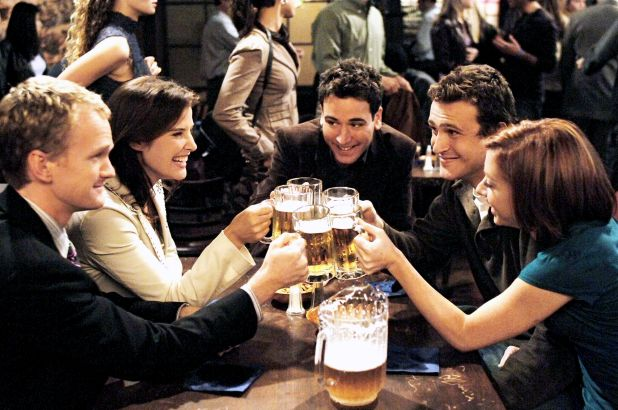 Image from the series 'How I Met Your Mother' with 5 friends clinking their pints of beer together in a bar.