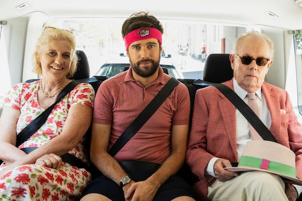 Image from the series 'Jack Whitehall: Travels with my Father'. Three people pose for the camera in the back of a car.
