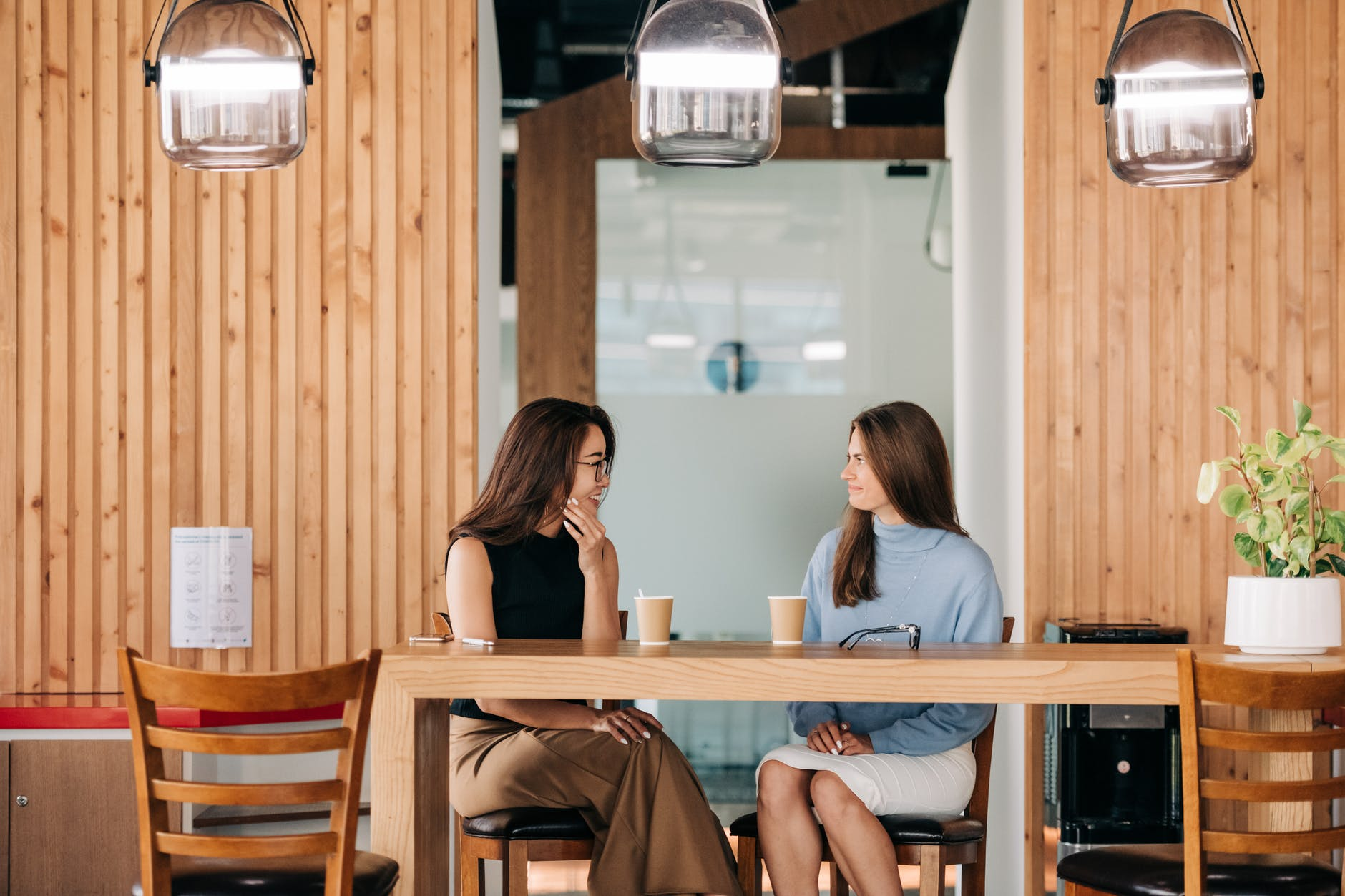 Two friends sit at a desk and chat with coffee.