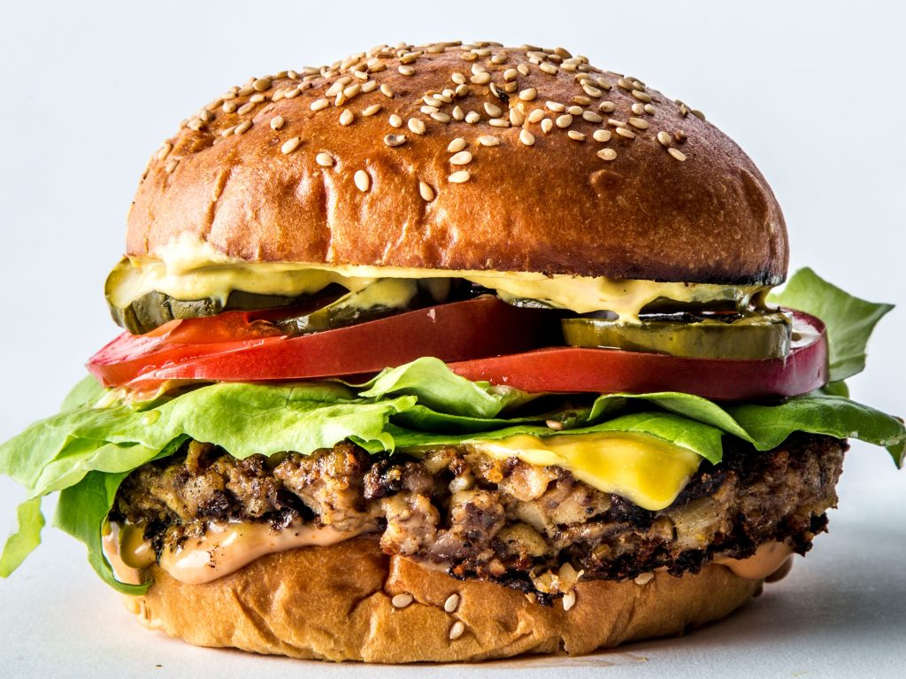 Burger in a bun, with lettuce and tomato.