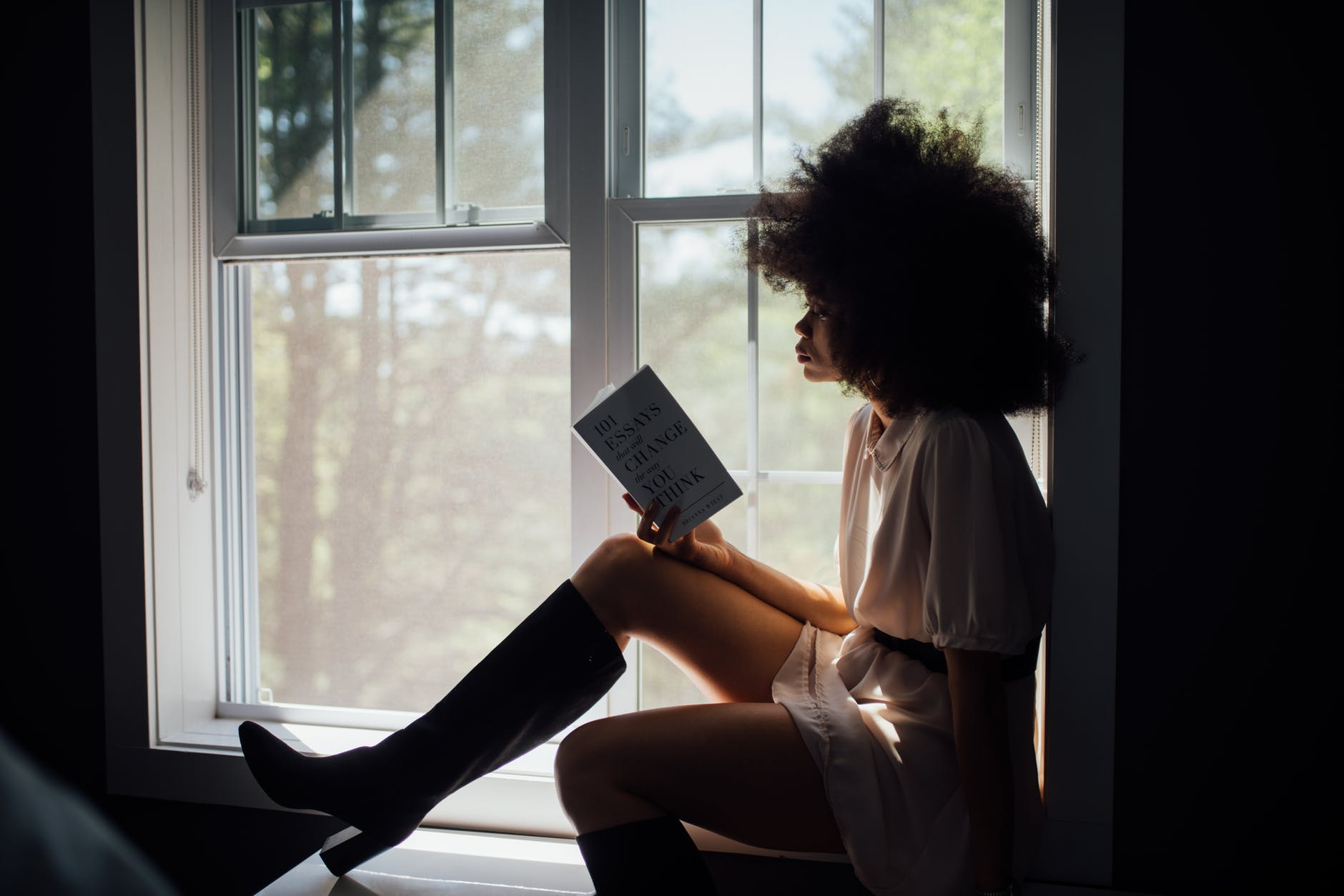 Woman sat on a windowsill reading a book. Her features are obscured by the light.