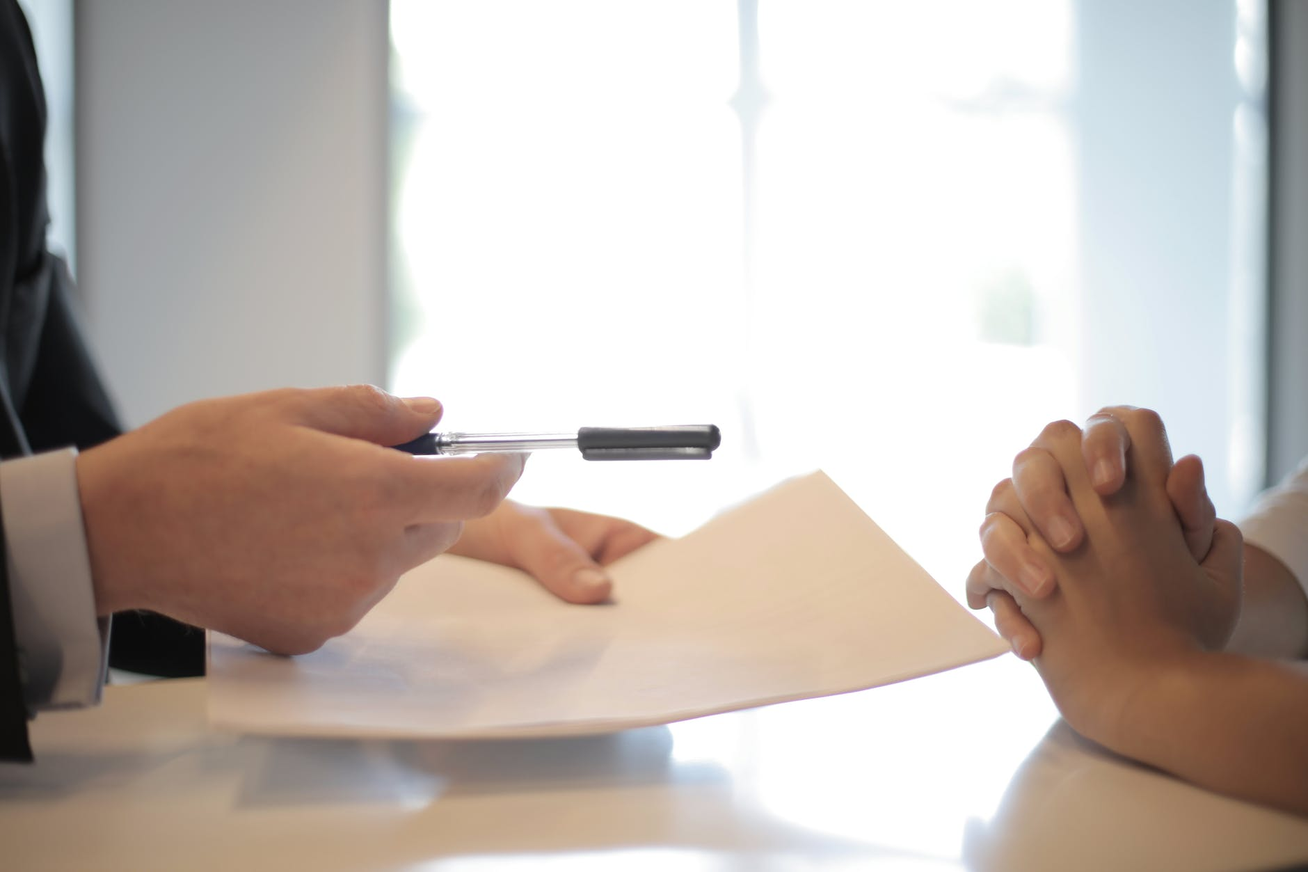Interview scene, just the applicant and interviewer's hands. The interviewer holds a piece of paper and pen.