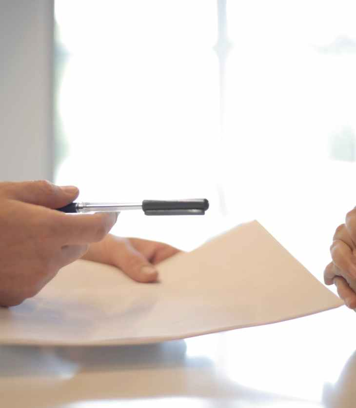 Interview scene, interviewer holds a piece of paper and pen