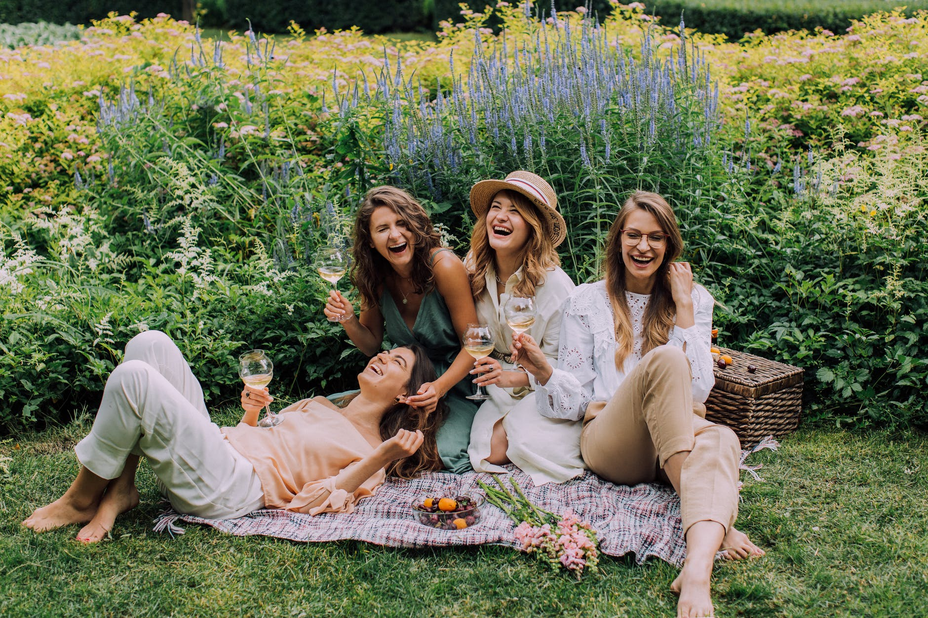 Four women laugh in a field with a picnic