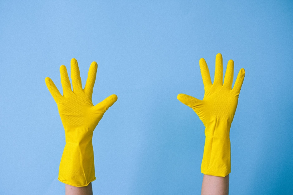 Two hands wearing yellow gloves, palms spread