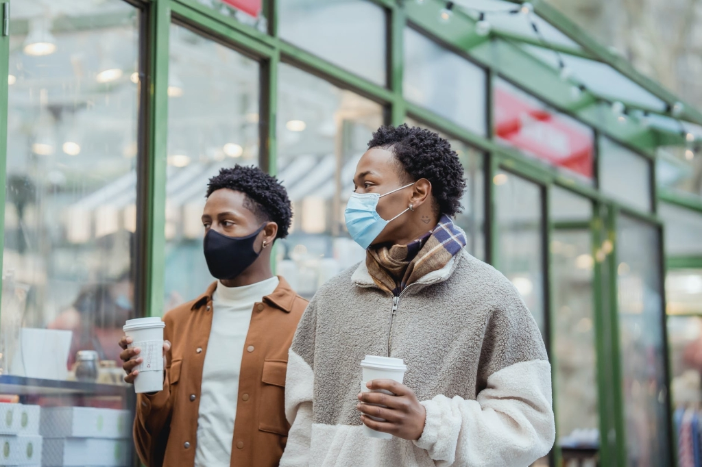 Two people walk outside with masks on, they hold disposable coffee cups