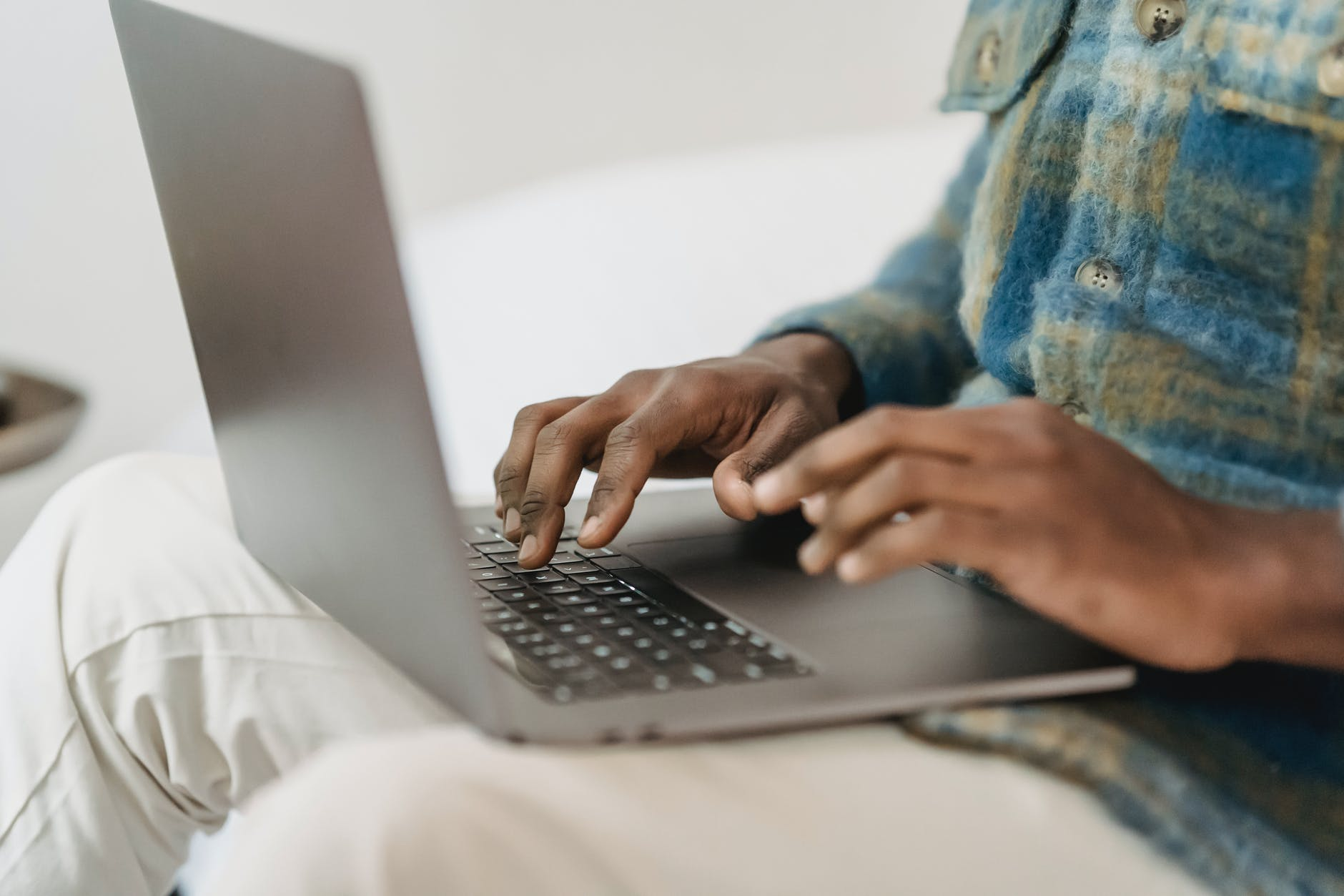 Man uses laptop on his knee, his face is not in the picture and the focus is on the laptop