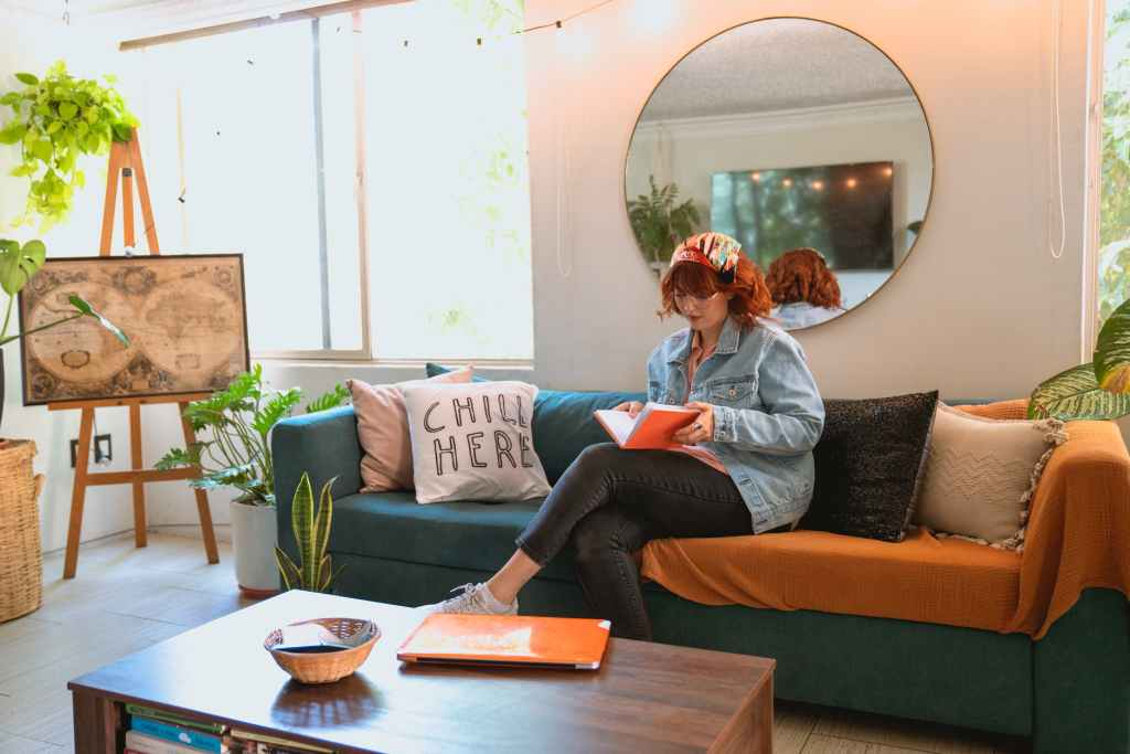 Woman sits on sofa and reads book with big mirror behind her.