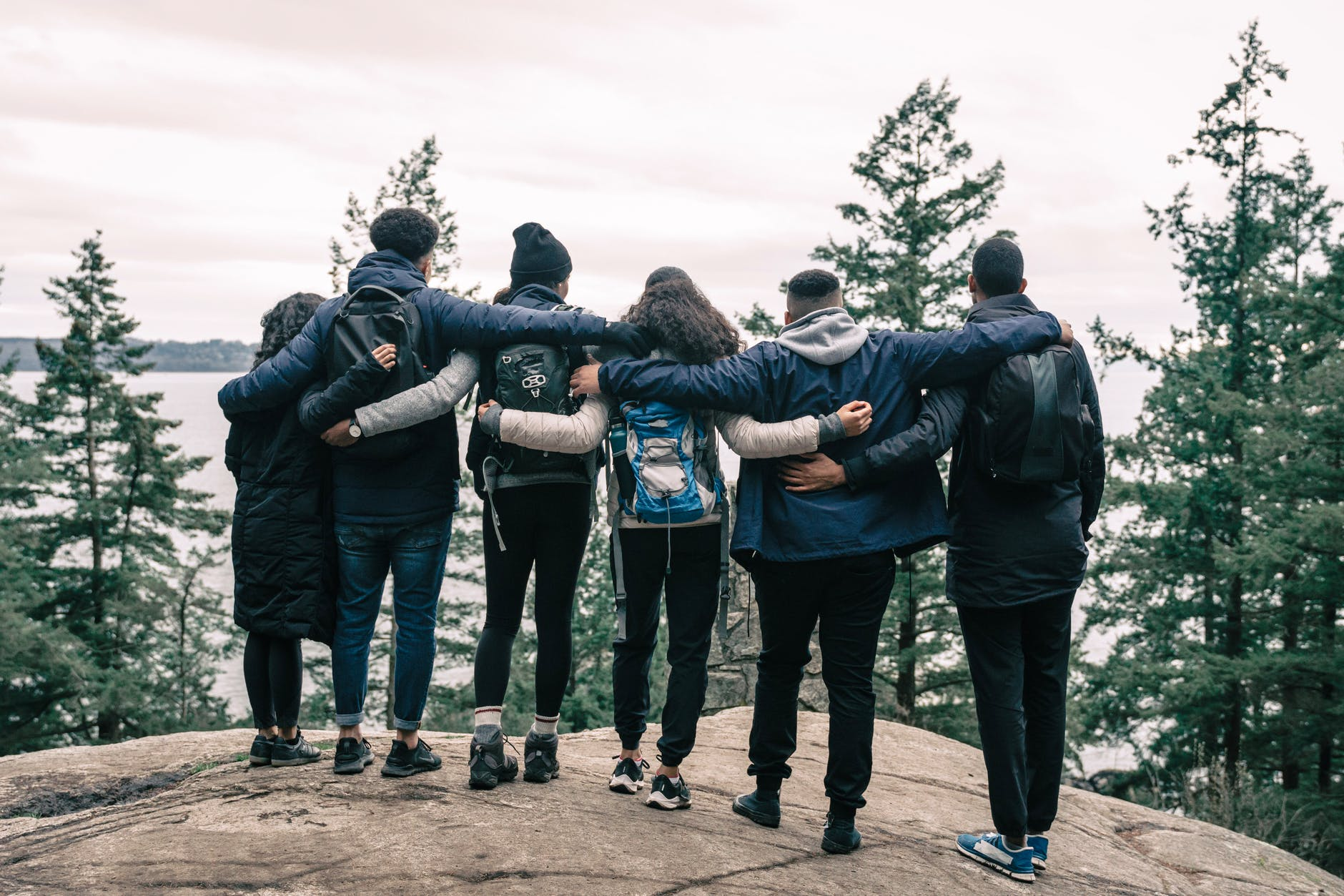 A group of friends stand on the edge of a forest, with their arms around each other. They have their backs to the camera