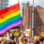 The top of a Pride march, hands holding Pride flags