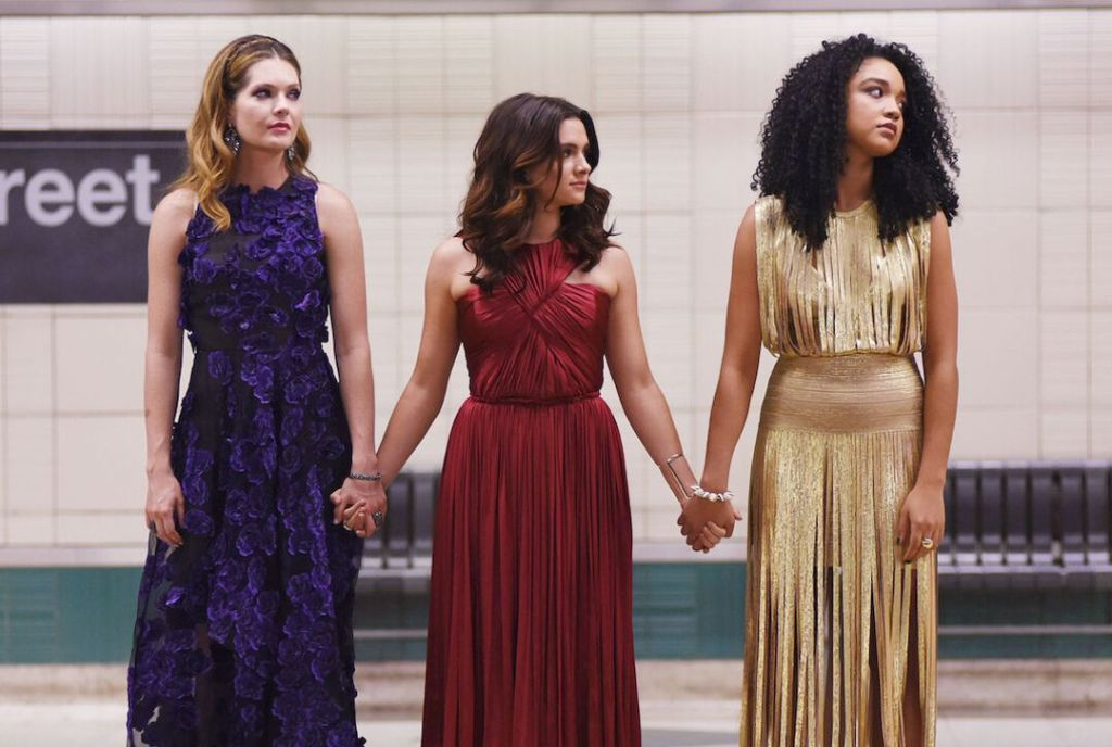 Three women from 'The Bold Type' wear glamorous dresses and hold hands on the side of the subway