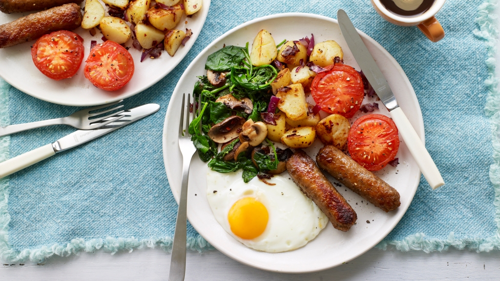 Vegetarian cooked breakfast, with sausages, eggs, and vegetables.