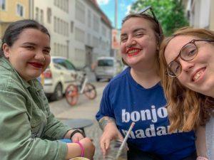 Three women smile outside a café