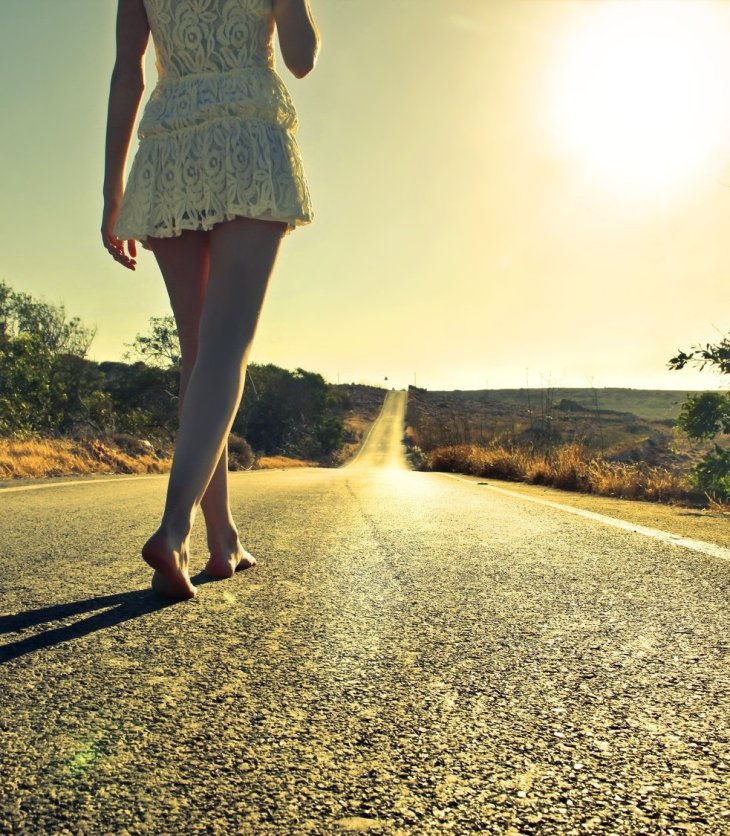 A woman walks down a path with no shoes on
