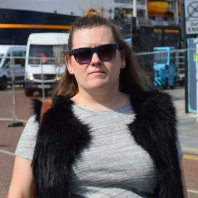 A woman stares into the camera, wearing sunglasses