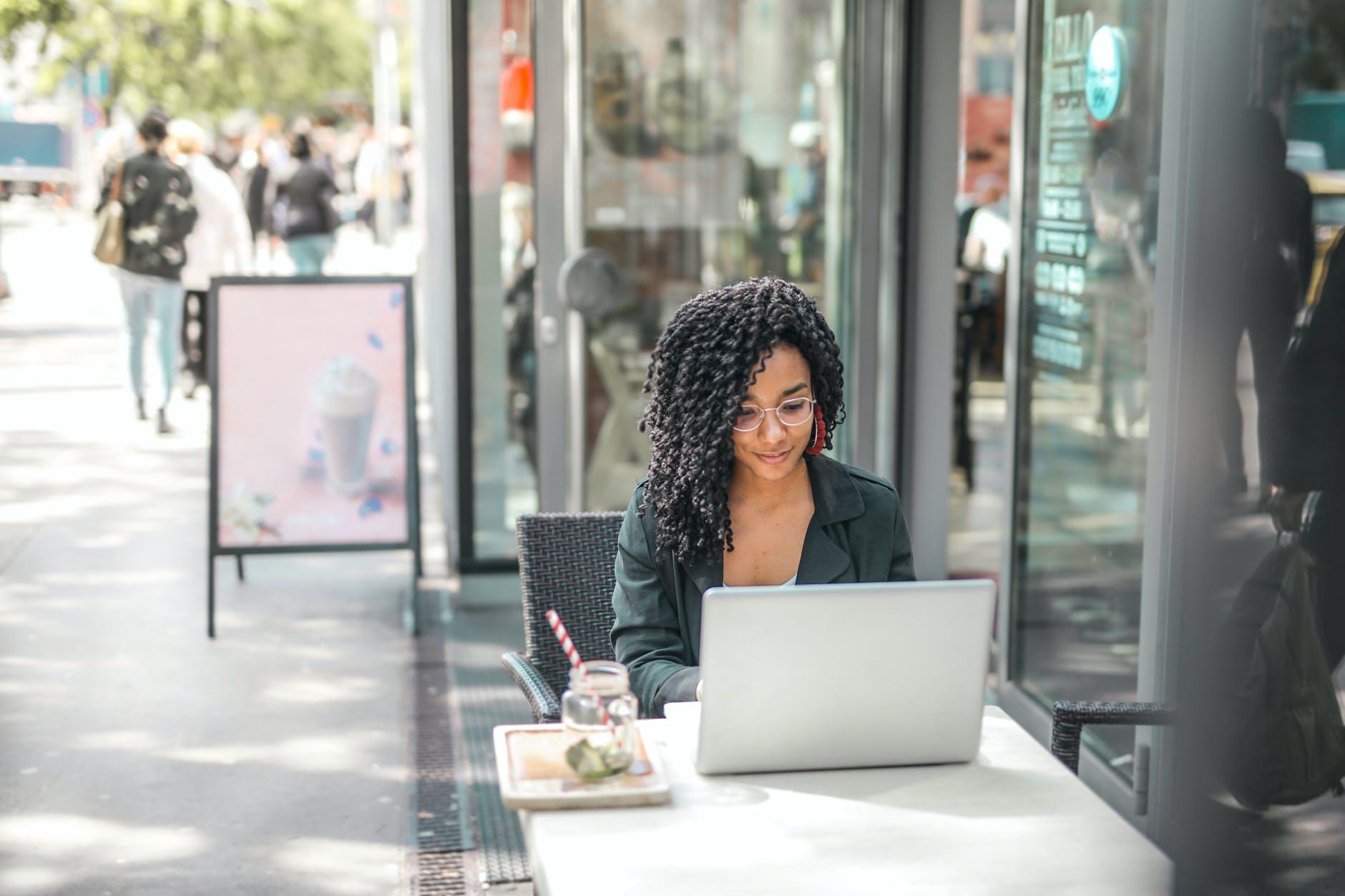 Woman uses laptop outside a café