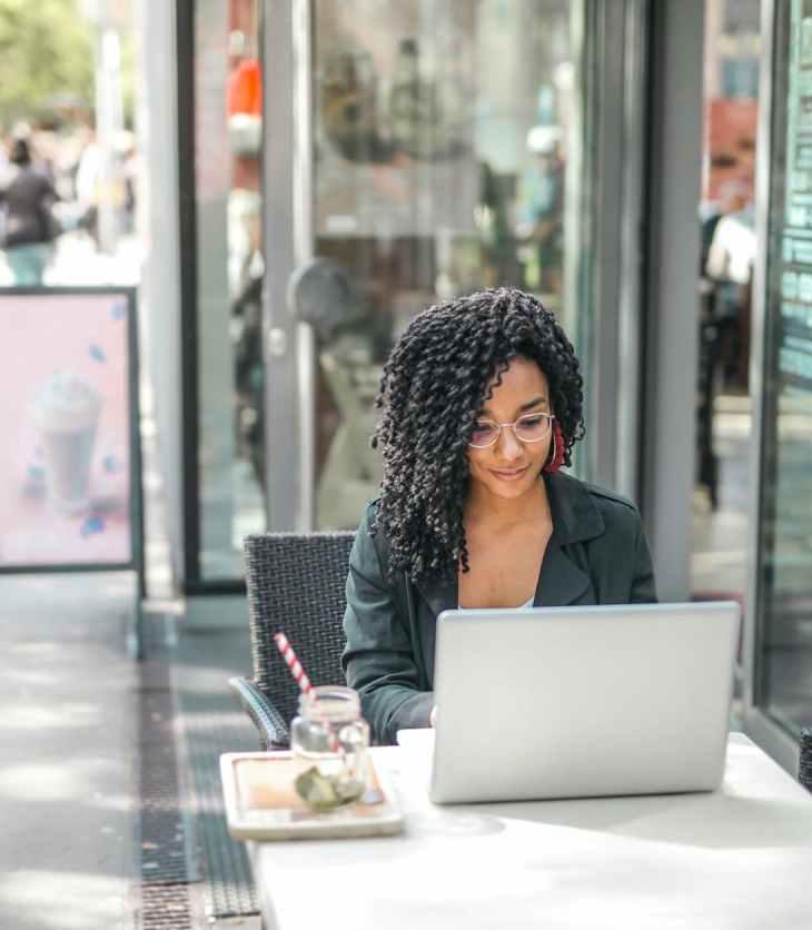 Young woman uses a laptop outside a café