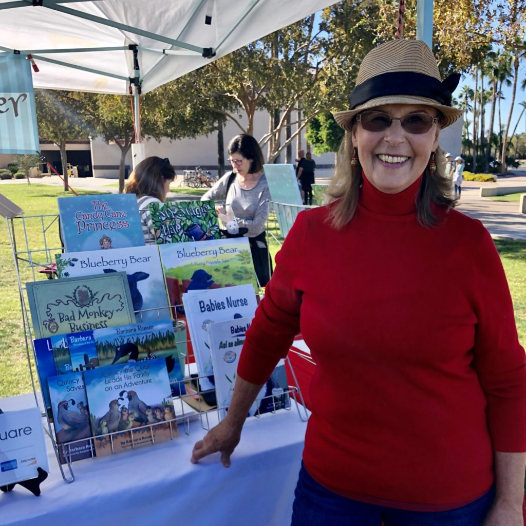 Female author stands in front of a book-stand with her children's books on it