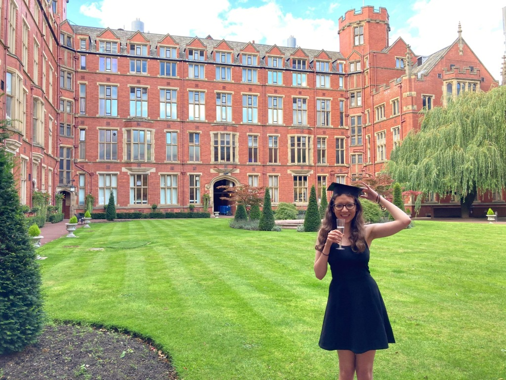 Young woman holds a fake graduation hat on her head and a glass of Prosecco. Smiles at the camera in front of a University building.