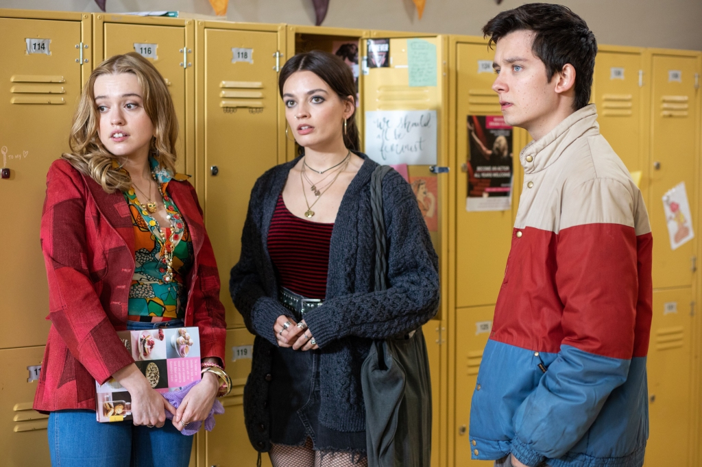 Three characters from the cast of 'Sex Education' stand by the lockers of a high school