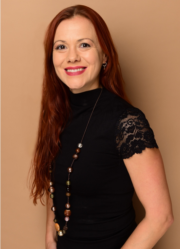 A woman with ginger hair smiles at the camera