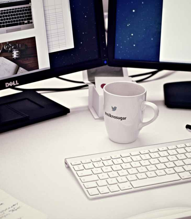 A white mug is between two laptops on a desk