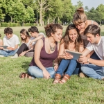 A group of friends sit on grass and look at a notepad or iPad