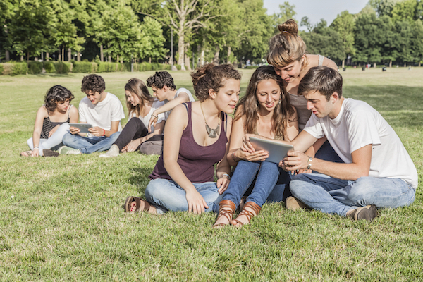 A group of friends sit on the grass looking at an iPad or notepad.