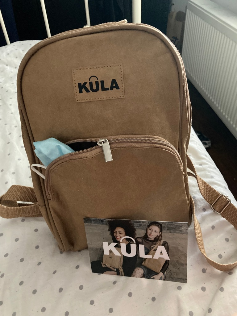 Brown Kula Bag with the front zipper open and a mask hanging out.