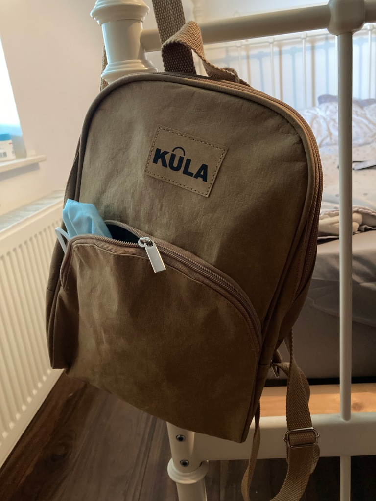 Brown Kula Bag hanging on the end of a bed frame. A mask hangs out of the front pocket.
