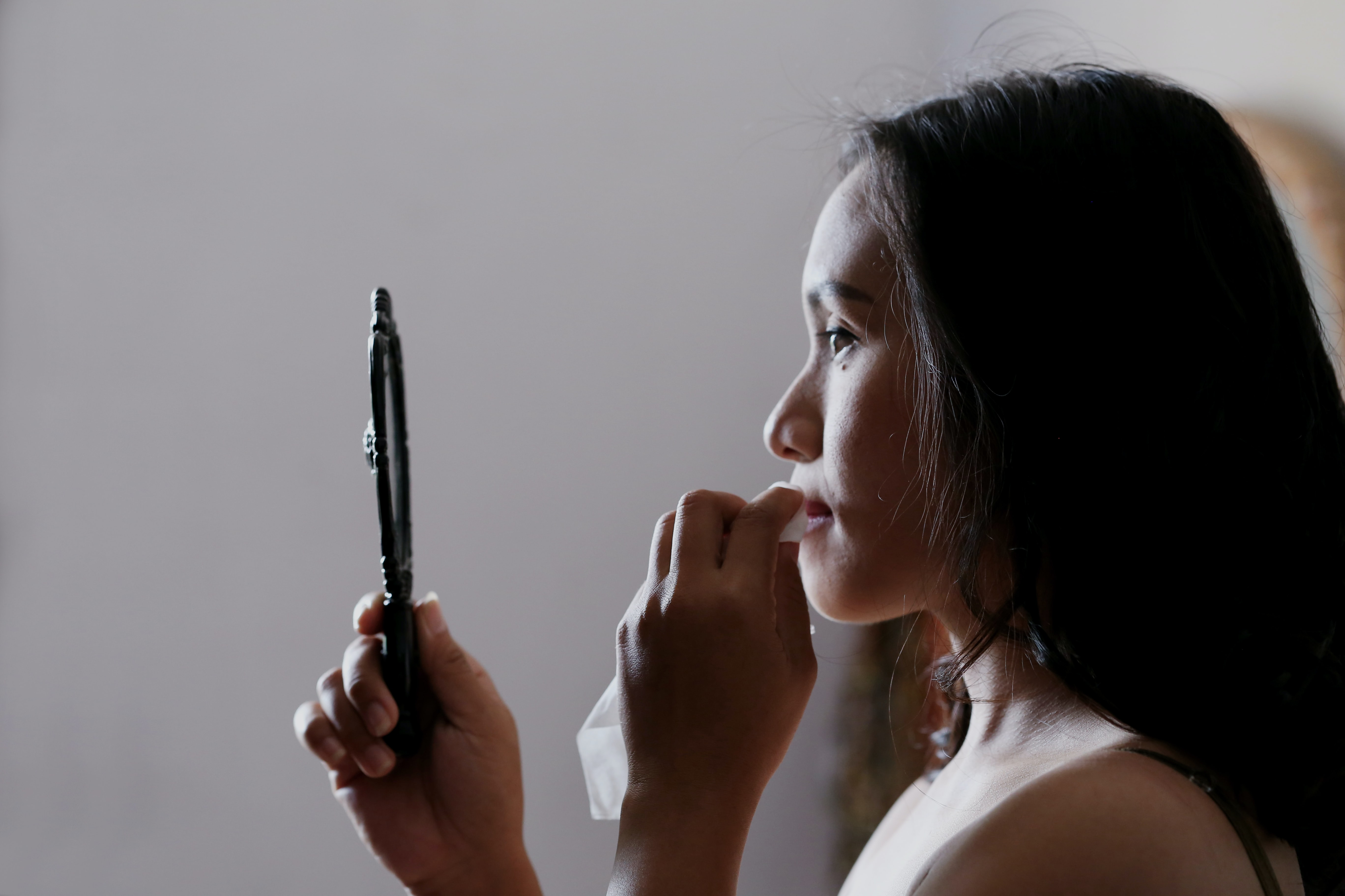 Woman takes off her make-up looking in the mirror