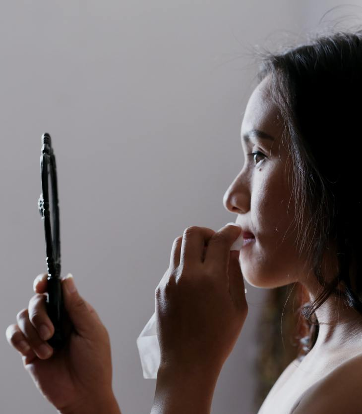 A woman using a make-up wipe to take off her make-up in the mirror