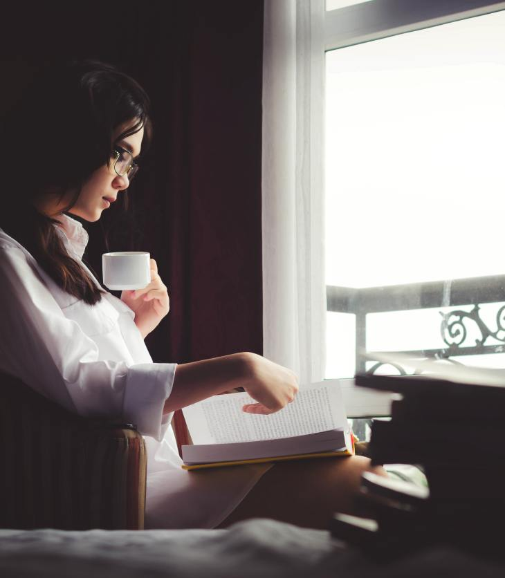 Woman reading alone by a window with a cup in her hand