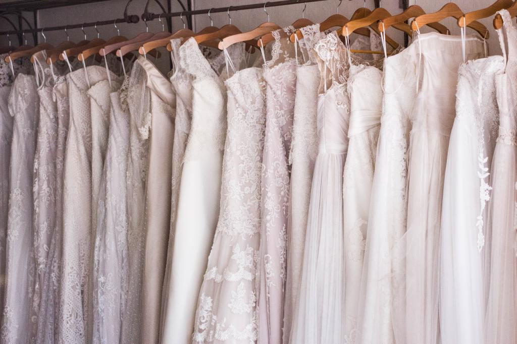 A stack of wedding dresses on wooden clothes hangers