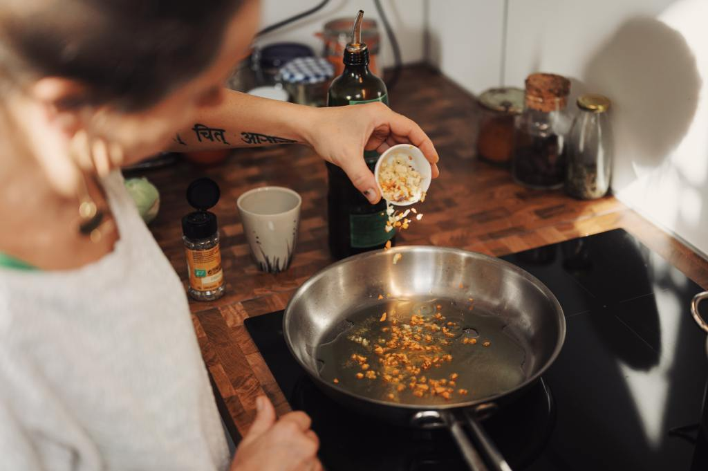 Woman pours ingredients into a frying pan