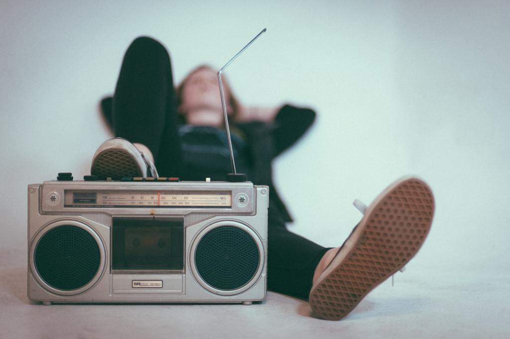 Person lays back and listens to a retro radio in the foreground