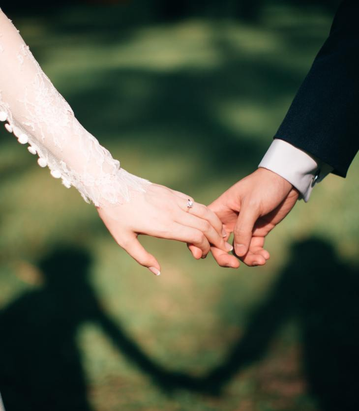 A person in a suit and a person in a white dress hold hands. The image shows only their hands.