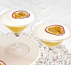 Two martini glasses, with a slice of passionfruit on top of foam.